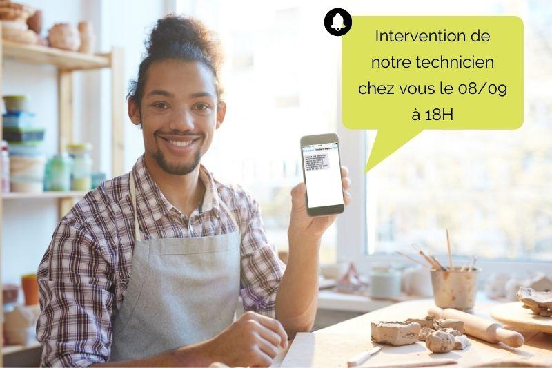 Agenda partagé avec le client : un homme dans sa cuisine recevant un SMS de notification de rendez-vous sur son mobile