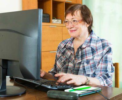 Dame, senior, utilisant un outil d'agenda partagé sur son PC